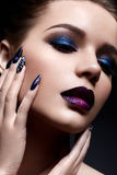 Young woman with creative make-up and violet lips with a gradient and sparkles on the face. Beautiful model with bright nails with Royalty Free Stock Image