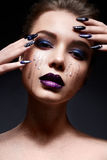Young woman with creative make-up and violet lips with a gradient and sparkles on the face. Beautiful model with bright nails with. Rhinestones. The beauty of Royalty Free Stock Image