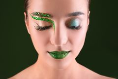 Young woman with creative makeup on background. Young woman with creative makeup on  background Stock Image