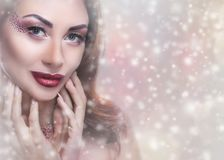 A young woman with creative makeup and beautiful hairstyle, on the background of snowflakes. New Year`s concept royalty free stock image