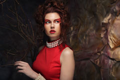 Young woman with creative visage wearing  red dress Stock Images