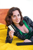 Young woman with credit card in bed Royalty Free Stock Image