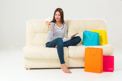 Young woman with credit card buying sitting on sofa with paper bags and new clothes. Shopping consumerism concept. Young woman with credit card buying sitting on Royalty Free Stock Photo
