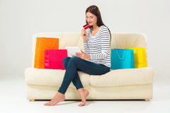 Young woman with credit card buying sitting on sofa with paper bags and new clothes Stock Photos