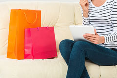 Young woman with credit card buying sitting on sofa with paper bags and new clothes Stock Images