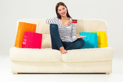 Young woman with credit card buying sitting on sofa with paper bags and new clothes Royalty Free Stock Photography
