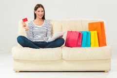Young woman with credit card buying sitting on sofa with paper bags and new clothes stock photography