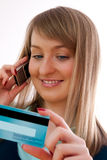 Young woman with credit card and cellphone Stock Photo
