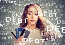 Young woman with credit card debt. Concerned woman looking at many credit cards scared with huge amount of debt Stock Photography