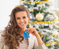 Young woman with credit card in front of christmas tree. Portrait of happy young woman with credit card in front of christmas tree Royalty Free Stock Image