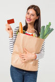 Young woman with credit card holding groceries. Beautiful young woman with credit card holding groceries in eco paper bag. Female consumer in shop. Concept of Stock Images