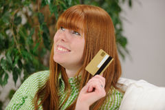 Young woman with credit card smiling Stock Image
