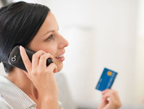 Young woman with credit card and speaking mobile Royalty Free Stock Photos