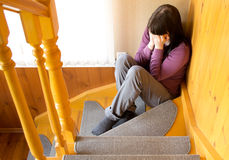 The young woman cries. In a ladder corner Royalty Free Stock Images