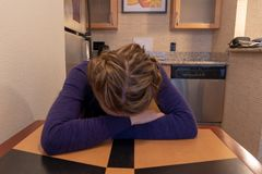 Young woman cries and buries her head and face in her arms while sitting at a kitchen table alone stock photo