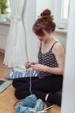 Young Woman Crocheting With Yarn on the Floor Royalty Free Stock Photography