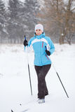 Young woman cross-country skiing in winter park Royalty Free Stock Photos