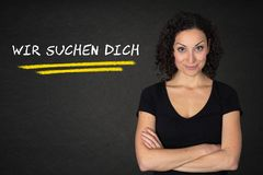 Young woman with crossed arms and `Wir suchen dich` text on a blackboard background. Translation: `We are looking for you` royalty free illustration