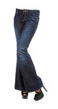 Young woman crossed legs in bell bottom jeans and platform peep. Toe stilettos isolated on white background. Clipping path included Stock Photos