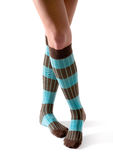 Young woman crossed legs posing with turquoise striped socks Stock Photo