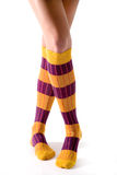 Young woman crossed legs posing with yellow striped socks Royalty Free Stock Photography