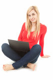 Young woman with crossed legs, using laptop Stock Images
