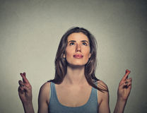 Young woman crossing her fingers looking up Royalty Free Stock Photos