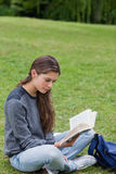 Young woman crossing her legs while reading a book Royalty Free Stock Photos