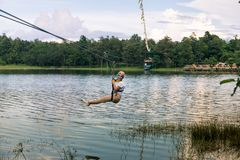 Young woman crossing a lake in zip line in Chiang Mai royalty free stock image