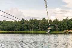 Young woman crossing a lake in zip line in Chiang Mai royalty free stock photography