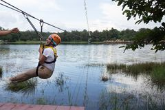 Young woman crossing a lake in zip line royalty free stock photography