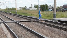 Woman crossing rail tracks. Young woman crossing rail tracks and coming to the platform to wait for suburban train stock video footage