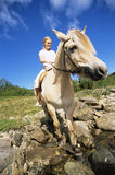 Young woman crossing a river by horse Royalty Free Stock Images