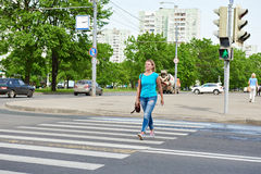 Young woman crossing road at green light Royalty Free Stock Image