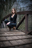 Young woman crouch at bridge Stock Photos