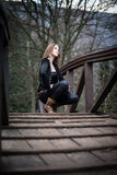 Young woman crouch at bridge.  Royalty Free Stock Photo