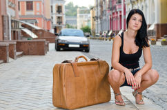 Young woman crouching alongside a suitcase. On the sidewalk in an urban street as she waits for her lift trip or vacation Stock Photos