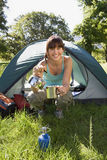 Young woman crouching beside dome tent in woodland clearing, taking boiled kettle from camping stove, smiling, portrait stock photography