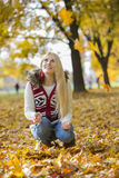 Young woman crouching while looking up in park during autumn Royalty Free Stock Image