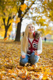 Young woman crouching while looking up in park during autumn Stock Image
