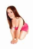 Young woman crouching. A lovely young Asian woman in a short pink dress crouching on the floor Stock Images