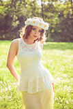 Young  woman with a crown of chamomiles on her head in the park Royalty Free Stock Images