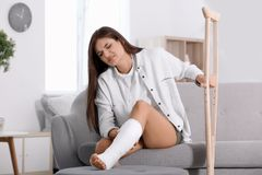 Young woman with crutch and broken leg in cas. T sitting on sofa at home stock photos