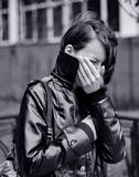 Young woman crying outdoors. Black and white side portrait of young woman in raincoat crying outdoors with hand over mouth Stock Photography