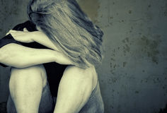 Young woman crying sitting on the floor stock image