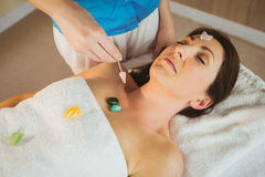 Young woman at crystal healing session. Young women at crystal healing session in therapy room Royalty Free Stock Images