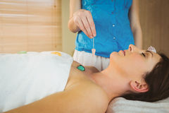 Young woman at crystal healing session. Young women at crystal healing session in therapy room Royalty Free Stock Photography