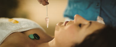 Young woman at crystal healing session. Young women at crystal healing session in therapy room Stock Photography