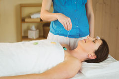 Young woman at crystal healing session. Young women at crystal healing session in therapy room Stock Image