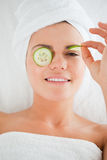 Young woman with cucumber slices on the face. In a spa Stock Photography